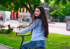 Beautiful woman with a vintage bicycle in a city park Stock Image