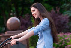 Beautiful woman with a vintage bicycle in a city park Royalty Free Stock Photo