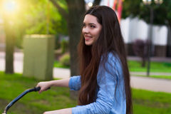 Beautiful woman with a vintage bicycle in a city park Stock Photo