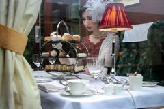 Beautiful woman in vintage clothing enjoying afternoon tea in train carriage royalty free stock photo