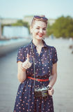 Beautiful woman in vintage clothing with retro camera showing th Stock Image