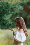 Beautiful woman in vintage dress beige. Cute girl in long dress walking in a pine forest. The style of the Queen. Royalty Free Stock Photo