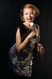 Beautiful woman in vintage style dress singing Stock Photo
