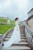 Beautiful woman in vintage wedding dress stay on stairs Royalty Free Stock Photography