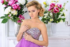 Beautiful woman in violet  dress in luxury studio. Royalty Free Stock Photo