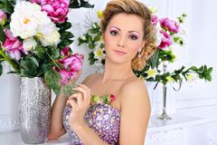 Beautiful woman in violet  dress in luxury studio. Stock Photos
