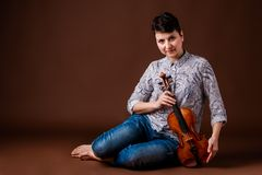 Woman with violin. Beautiful woman with violin on dark brown background Royalty Free Stock Photos