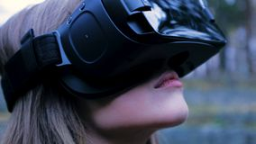 Beautiful woman with virtual reality in outdoor park. VR headset glasses device. Young woman in a VR glasses in the Park stock photo