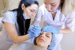 Beautiful woman visiting professional dermatologist and cosmetologist for permanent makeup. Cute women visiting professional cosmetologist and dermatologist for stock photo