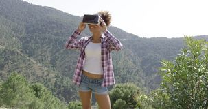 Beautiful woman in VR glasses on nature. Young woman standing on top of mountain in VR headset and looking around on background of mountains stock footage