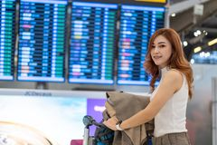 Woman waiting for flight with information board in airport royalty free stock image