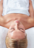 Beautiful woman waiting for massage at wellness spa. Vertical shot of beautiful woman waiting for a massage at a wellness spa, with focus on face royalty free stock images