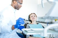 Beautiful woman waiting for an oral cavity checkup. Nice patient. The focus being on a pretty cheerful young women sitting in a dentist chair and smiling at the Royalty Free Stock Image