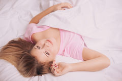 Beautiful woman waking up in the bed Stock Images