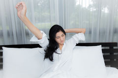 Beautiful woman waking up in her bed Stock Images