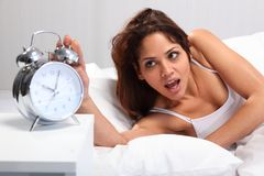 Beautiful woman waking up reaching for alarm clock Royalty Free Stock Photos