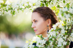 Sad beautiful fashion woman in a spring garden Royalty Free Stock Images