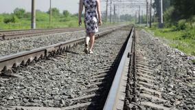 Beautiful woman walking along railway tracks in a sun day.  stock video