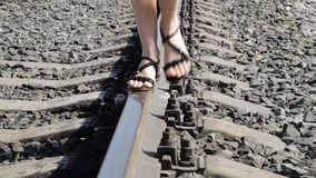 Beautiful woman walking along railway tracks in a sun day.  stock footage