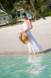 Beautiful woman walking along seaside on tropical beach Stock Image