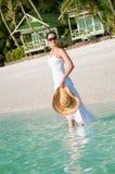 Beautiful woman walking along seaside on tropical beach royalty free stock image