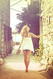 Beautiful woman walking barefoot in the street, cross process Stock Image