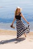 Beautiful woman walking on the beach Stock Photography
