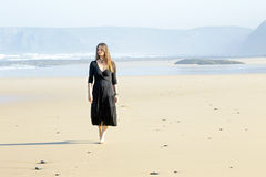 Beautiful woman walking on the beach Royalty Free Stock Photos