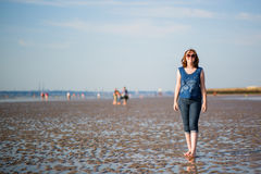 Beautiful woman walking on the beach at low tide Royalty Free Stock Photos