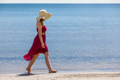 Beautiful woman walking on the beach Stock Images