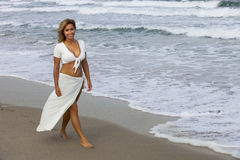 Beautiful woman walking on beach Stock Photography