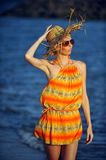 Beautiful woman walking on the beach. Stylish model wearing fashionable straw hat and sunglasses, luxury summer vacation concept Royalty Free Stock Photos