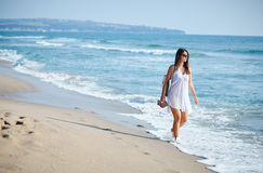 Beautiful woman walking on a beach Stock Photo