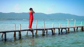 Beautiful woman walking down pier in long red dress. Phu Quoc Island. The woman costs on a pier with the straightened. The woman goes along transparent turquoise stock video footage