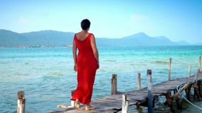 Beautiful woman walking down pier in long red dress. Phu Quoc Island. Landscape of mountains and sea. The woman walks on. The woman goes along transparent stock video