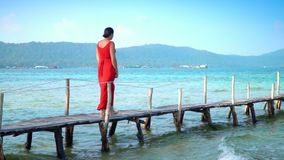Beautiful woman walking down pier in long red dress. Phu Quoc Island. Slow mothion. The traveler walks on a pier on. The woman goes along transparent turquoise stock video footage