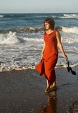 Beautiful woman walking with dress by the seaside Stock Photo