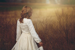 Beautiful woman walking in a field Royalty Free Stock Photography