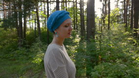 Beautiful woman walking in the forest in blue turban, sun flares behind.holidays concept stock video footage