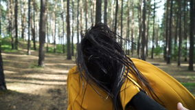 Beautiful woman is walking in the forest. Slowmotion. A woman is walking in the forest with a man. A young couple is resting in the park. Slowmotion stock video footage