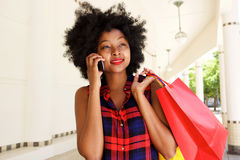Beautiful woman walking with mobile phone with shopping bags Stock Photo
