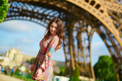 Beautiful woman walking in Paris under the Eiffel tower on a nice spring or summer day Royalty Free Stock Images