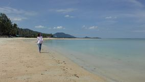 Beautiful Woman walking by the Shore Line at the Beach. Of Tropical Island stock video footage