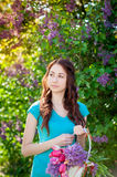 Beautiful woman walking in the spring garden with a basket of flowers Royalty Free Stock Images
