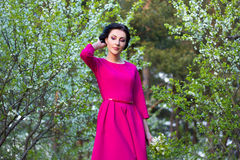 Beautiful woman walking in spring garden with blooming cherry tr Stock Image