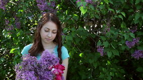 Beautiful woman walking in spring park with a bouquet of lilac.  stock video