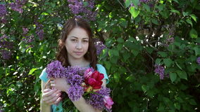 Beautiful woman walking in spring park with a bouquet of lilac.  stock video footage