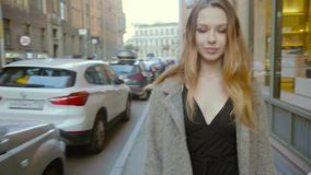 Beautiful woman walking on the street near the boutiques. Woman elegantly walking with confidence. Slow motion stock video