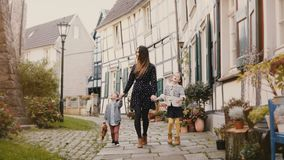 Beautiful woman walking with two children. Holding hands. European mother, girl and boy together. Hattingen, Germany 4K. Beautiful woman walking with two stock video footage