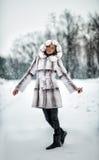 Beautiful woman walking through winter road Royalty Free Stock Photo